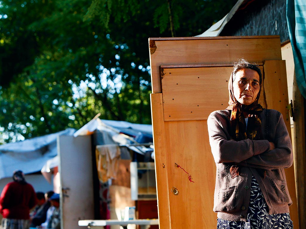 A woman stands at the entrance of a shack in a Roma camp in Evry, outside Paris