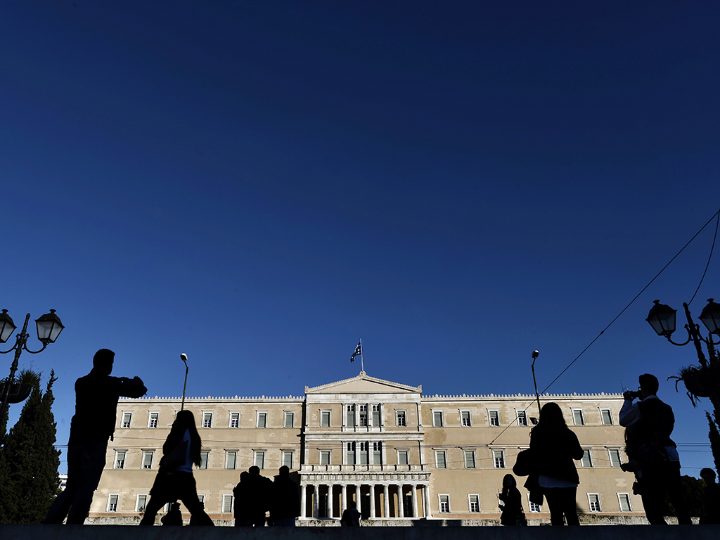People stand by the Greek parliament in Athens. Many expect the country to be unable to obtain bailout funds by the end of this week, which is likely to throw its future into chaos