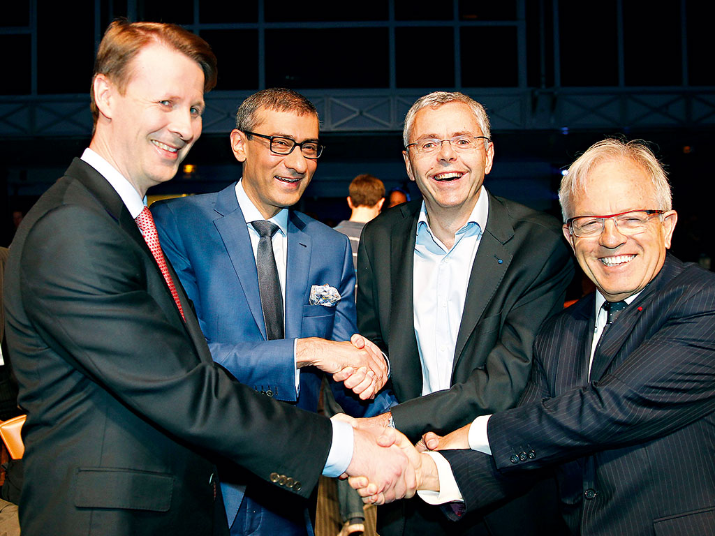 Rajeev Suri (centre left) meets executives from Alcatel-Lucent, after agreeing the Nokia's takeover of the company